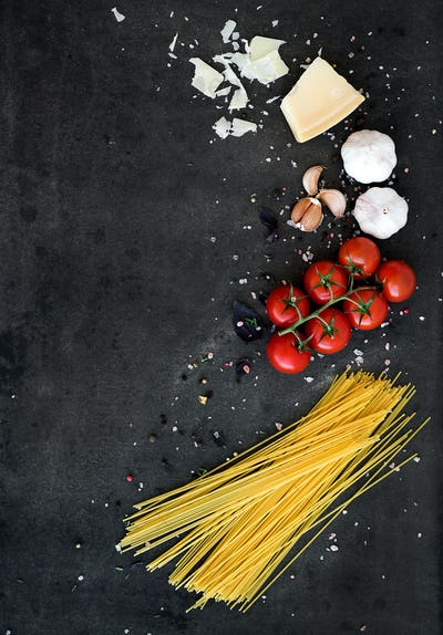 Food frame. Pasta ingredients. Cherry-tomatoes, spaghetti pasta, garlic, basil, parmesan and spices