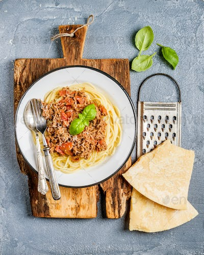 Pasta dinner. Spaghetti Bolognese in metal plate on rustic wooden board
