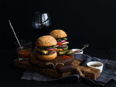 Fresh beef burgers on rustic wooden boards with glass of wine and tomato sauce, black background.