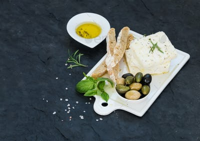 Fresh feta cheese with olives, basil, rosemary and bread slices on white ceramic serving board