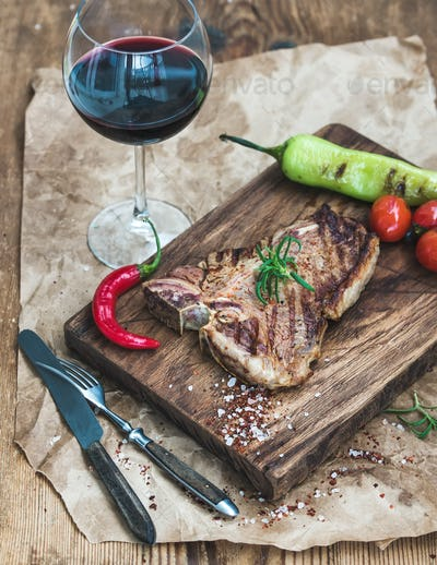 Cooked meat t-bone steak on serving board with roasted tomatoes, chili peppers