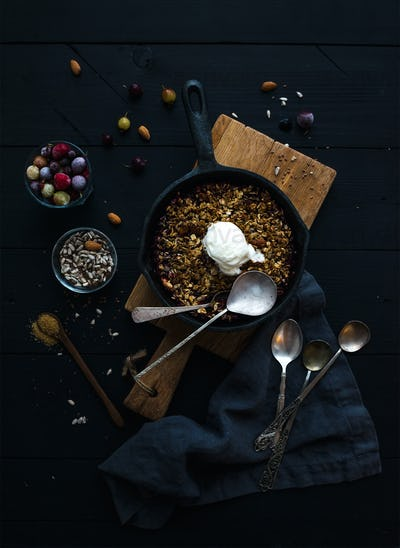 Oat granola crumble with frozen fresh berries, seeds and ice-cream scoop in iron skillet pan