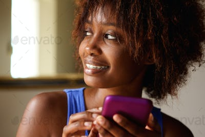Close up smiling young african woman with cell phone
