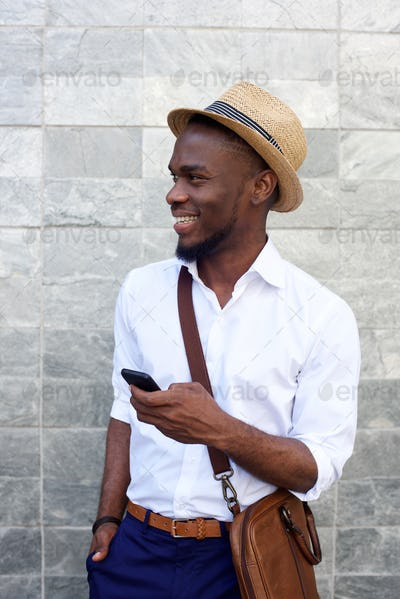 Young african man smiling against gray wall with mobile phone