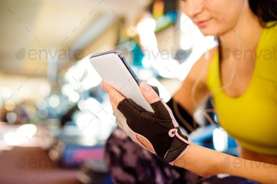 Attractive fit woman in a gym with smart phone