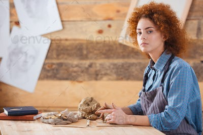 Pretty young woman sitting and working in pottery studio