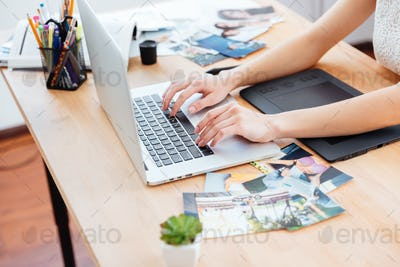 Woman photograper typing on laptop keyboard and using graphic tablet