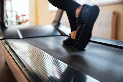 Treadmill used by sportswoman for running in gym