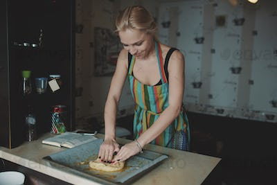 Woman cooking pizza at kitchen