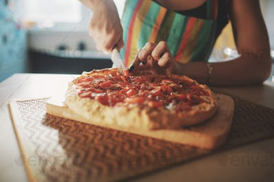 Young woman with a knife cut the pizza