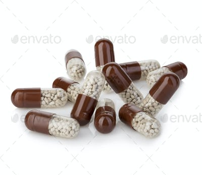 Brown capsules, pills close-up on a white background.