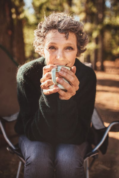 Mature caucasian woman having coffee at campsite