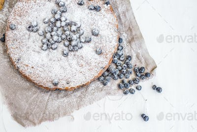 Blueberry cake with fresh blueberries and sugar powder on a beig