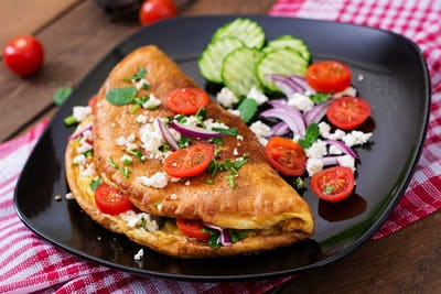 Omelet with tomatoes, parsley and feta cheese on black plate.