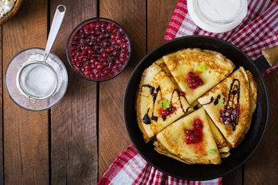 Golden pancakes with cranberry jam and honey in a rustic style. Top view
