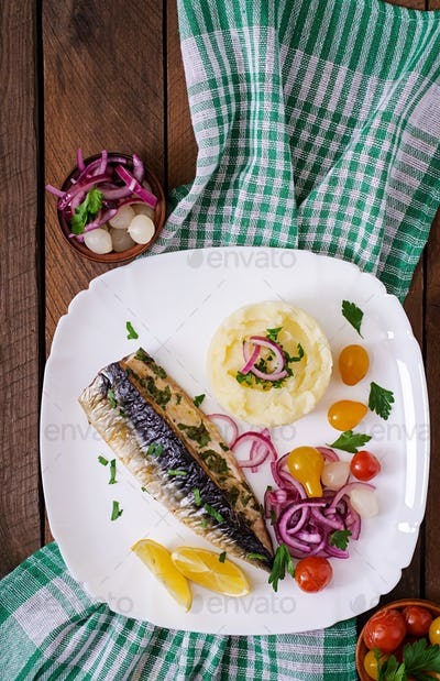 Baked mackerel with herbs and garnished with mashed potatoes and pickled vegetables. Top view