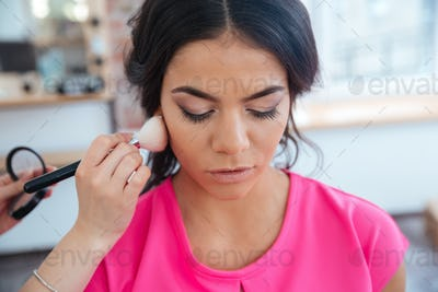 Makeup artist doing makeup to thoughtful pretty young woman