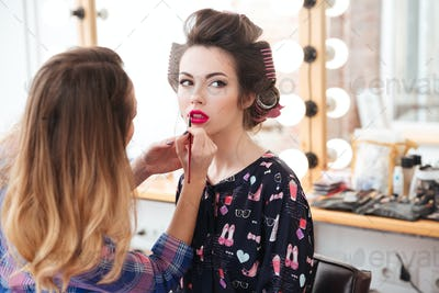 Woman professional visagist doing makeup with pink lipstick to model