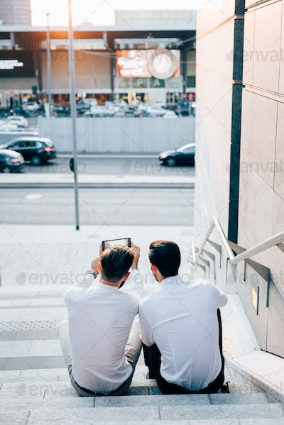 Rear view of two young modern businessman, sitting on a staircas