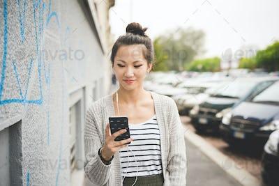 young beautiful asiatic woman holding a smart phone listening mu