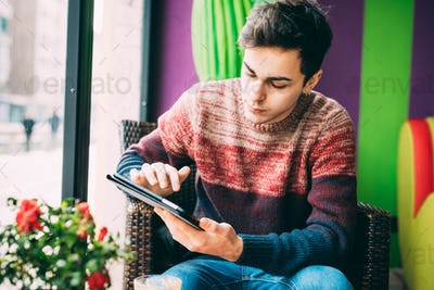 Young handsome caucasian man sitting in a bar, holding a tablet,