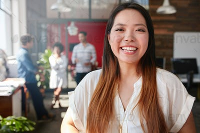 Cheerful young asian woman standing in office