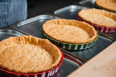 Cooked pie bases in baking pans on the kitchen