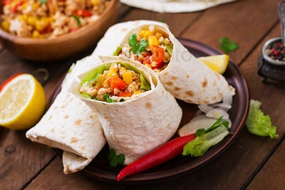 Burritos wraps with chicken meat, corn, tomatoes and peppers on wooden background