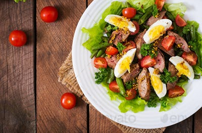Warm salad with chicken liver, green beans, eggs, tomatoes and balsamic dressing. Top view