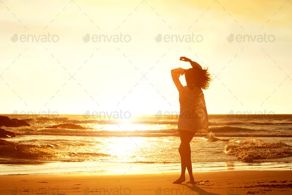 Silhouette young woman walking on beach during sunset