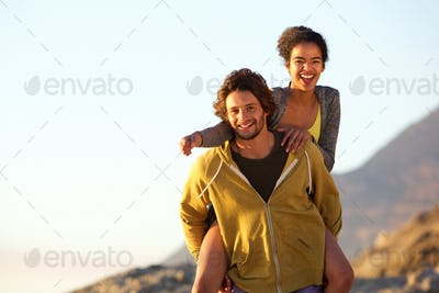 Smiling young man carrying carefree woman on back