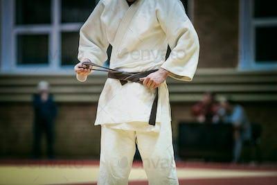 young judoka tying belt
