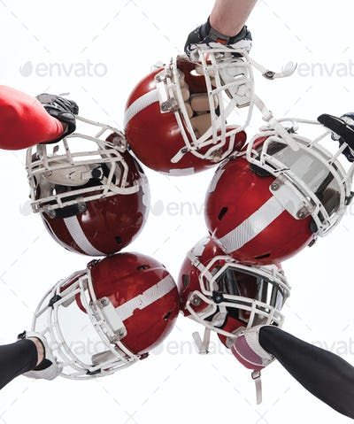 The hands of american football players with helmets on white background