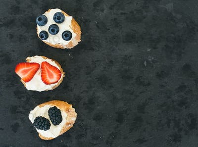 Goat cheese and berries mini-sandwitches on a dark stone backgro