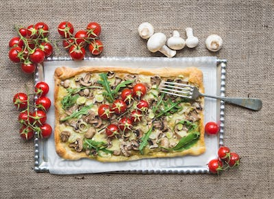 Rustic square mushroom pizza with fresh arugula and cherry-tomat