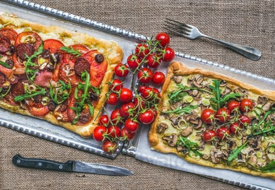 Two square pizzas with fresh arugula and cherry-tomatoes on silv