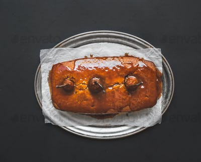 Spicy pear cake with caramel topping on a silver dish on dark su