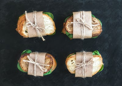 Chicken and spinach sandwiches wrapped in craft paper over a dar