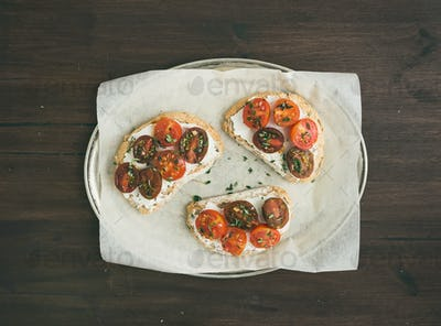 Ricotta and cherry-tomato sandwiches with fresh thyme on a silve