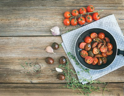 Roasted cherry-tomatoes with garlic and thyme in a cooking pan o