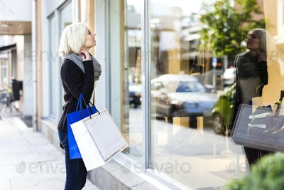 Blonde woman shopper with paper bags in the city