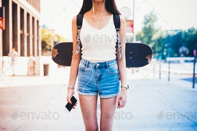 From the neck down view of young woman with skateboard and backp