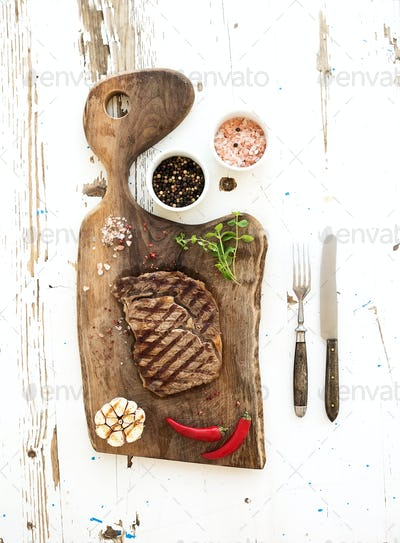 Grilled ribeye beef steak with herbs and spices on walnut cutting board