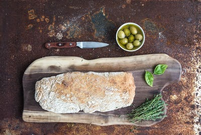 Freshly baked homemade ciabatta bread with olives, basil and thyme on walnut wood board