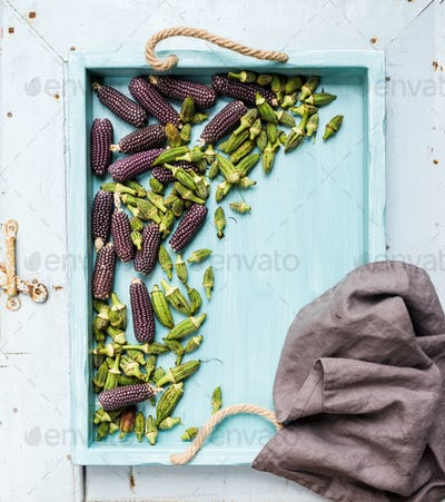Okra and small black corns on blue wooden tray over light rustic backdrop, top view.