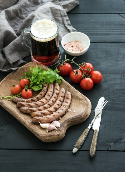 Grilled sausages with vegetables on rustic serving board and mug of light beer