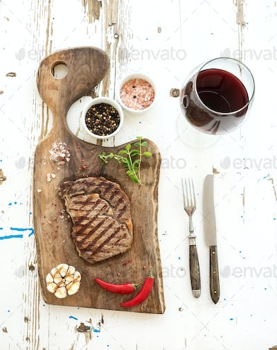 Grilled ribeye beef steak with herbs, spices and glass of red wine