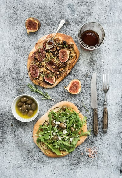 Rustic homemade pizzas with eggpant, cheese, olives, arugula, prosciutto and figs