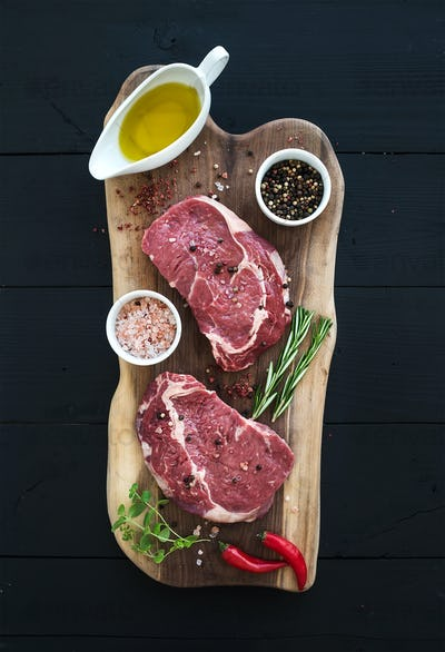 Raw fresh meat Ribeye steak entrecote and seasonings on cutting board over dark wooden background.