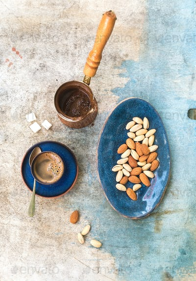 Black coffeee with almonds and pistachios over light blue backdrop. Top view